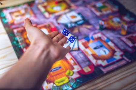 Foto de Hand throws the dice on the background of colorful blurred fantasy Board games, gaming moments in dynamics - Imagen libre de derechos