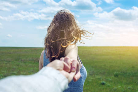 Photo pour Follow me, Attractive brunette girl holding the hand of the leads in a clean green field, steppe with clouds. The concept of the journey to the meeting of the nature - image libre de droit