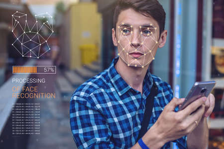 Photo pour Biometric verification. Modern young man with the phone. The concept of a new technology of face recognition on polygonal grid is constructed by the points of IT security and protection - image libre de droit