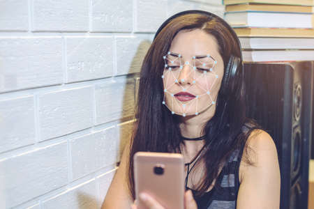 Photo pour Biometric verification. Modern young woman with the phone. The concept of a new technology of face recognition on polygonal grid is constructed by the points of IT security and protection - image libre de droit