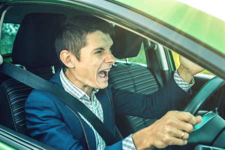 Photo pour Angry man driver screaming in the car. The quarrel and dissatisfaction on the way. - image libre de droit