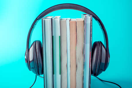 Photo for Black headphones with a stack of books on a blue background. The concept of audiobooks and modern education - Royalty Free Image