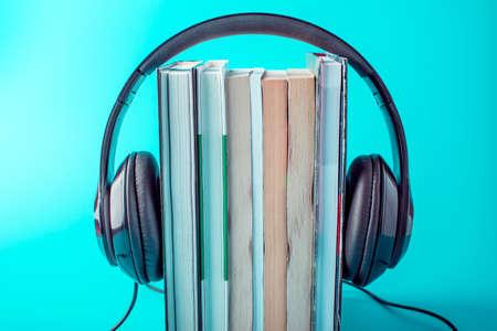 Foto de Black headphones with a stack of books on a blue background. The concept of audiobooks and modern education - Imagen libre de derechos