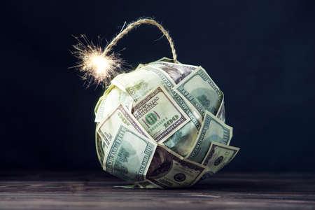 Foto de Big bomb of money hundred dollar bills with a burning wick. Little time before the explosion. The concept of financial crisis - Imagen libre de derechos