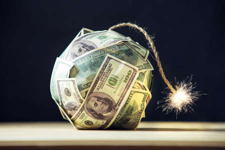 Foto de Big bomb of money hundred dollar bills with a burning wick. Little time before the explosion. The concept of financial crisis - Imagen libre de derechos