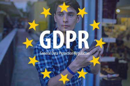 Foto de General Data Protection Regulation GDPR . The text with the EU flag in the background a man uses a mobile phone - Imagen libre de derechos