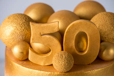 Photo pour A beautiful cake for the 50th anniversary of the wedding decorated with gold balls and rings. The concept of festive desserts - image libre de droit