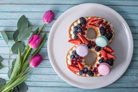 Foto de Homemade cake in shape of number 8 decorated with white cream and berries and flowers tulips. Sweet dessert as a gift for women's day on the eighth of March - Imagen libre de derechos