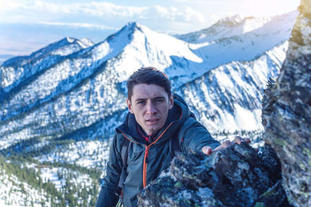 Photo pour Man Hiking with a backpack crawling on rocky rocks to the top on the background of snowy mountains. Concept the hard way and goal achievement - image libre de droit