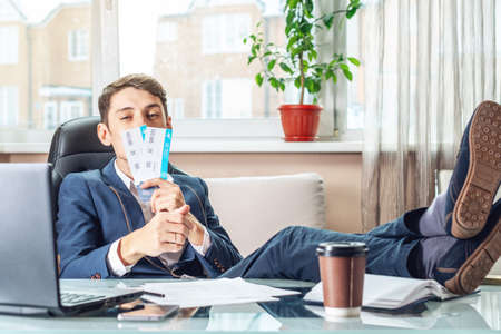 Foto de The young man is holding the won tickets. The joy of waiting for the journey. The concept of the office on vacation - Imagen libre de derechos