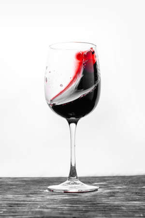 Foto de The red wine in the glass splashes in action on a white background. Stylish design card - Imagen libre de derechos