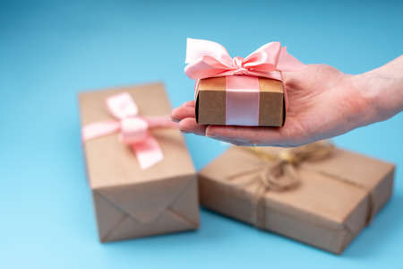 Photo pour Women's hands holding gift box Packed in Kraft paper with pink ribbon on blue background. Concept holiday card for Valentine's day and women's day - image libre de droit
