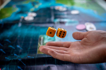 Photo for The hand throws yellow dice on the playing field. Luck and excitement. The concept of Board games. Gaming moments in dynamics - Royalty Free Image