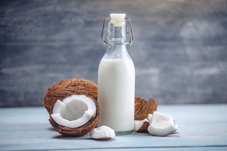 Photo pour Coconut milk in a bottle in a composition with an open coconut with white flesh on a blue wooden background. Organic healthy dietary vegan product used in cosmetology and Spa - image libre de droit