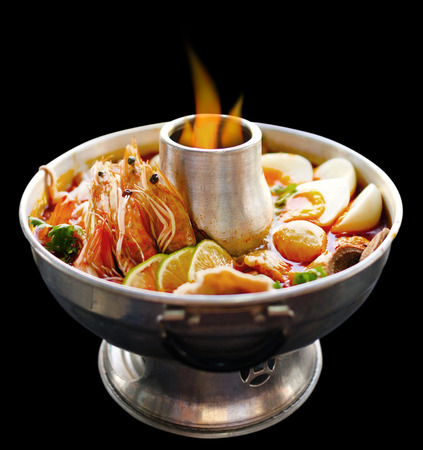 Photo for Thai Spicy herbal soup (Tom Yum) served in hot pot on fire - Royalty Free Image