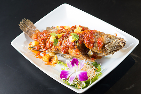 Photo for Thai Tradition Food: deep-fried fish topped with fresh herbs and sweet spicy sauce on plate - Royalty Free Image