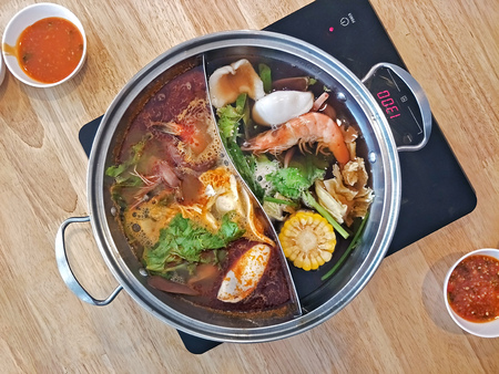 Photo pour japanese hot pot shabu with double side pot with spicy and soya black soup separate on each side on induction stove - image libre de droit
