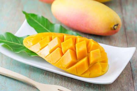 Foto de fresh mango fruit in white plate on wooden table - Imagen libre de derechos