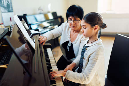 Foto de a music teacher with the pupil at the lesson piano - Imagen libre de derechos