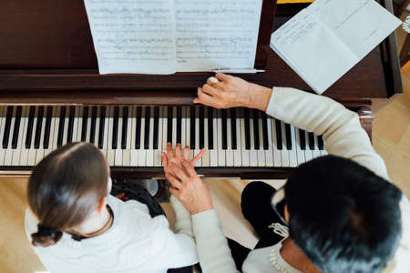 Foto de a music teacher with the pupil at the lesson piano, top view - Imagen libre de derechos