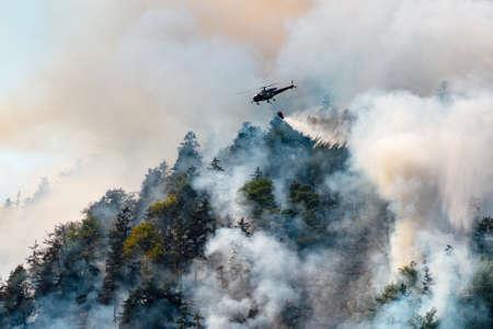 Foto de helicopter extinguishes forest fire on the slope of a fuming mountain - Imagen libre de derechos