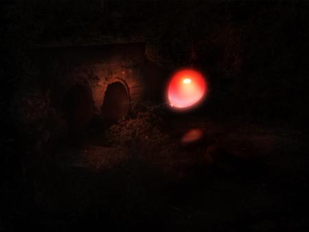 Foto de Glowing red balloon comes out from old concrete culvert in the night. - Imagen libre de derechos