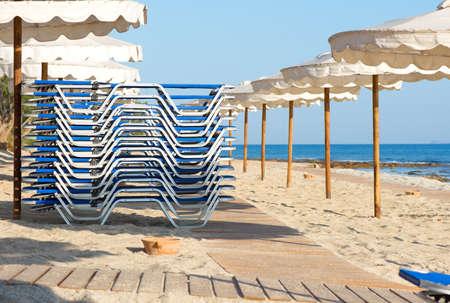 Foto de Sunbeds folded and umbrellas on the beach - Imagen libre de derechos
