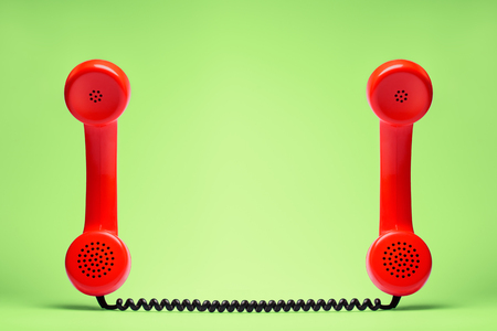 Photo for Two red telephone in retro style on green background. - Royalty Free Image
