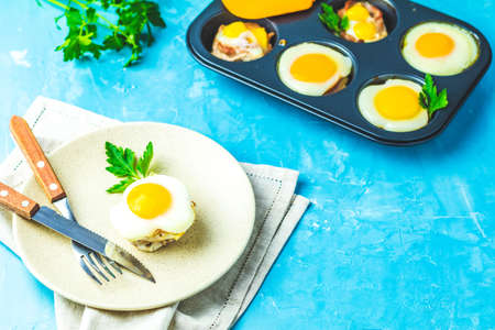 Photo pour Baked eggs  in light plate and baking molds. Portioned casserole from bacon  and eggs in Italian style. Blue concrete table surface background. - image libre de droit
