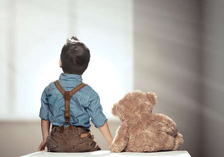 Photo pour Rear view of small boy with bear - image libre de droit