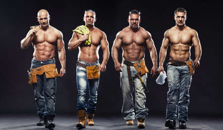 Photo for Group of young handsome builder posing, on dark background - Royalty Free Image