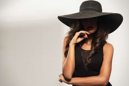 Photo pour Beautiful young woman with red lips wearing summer black hat with large brim - image libre de droit