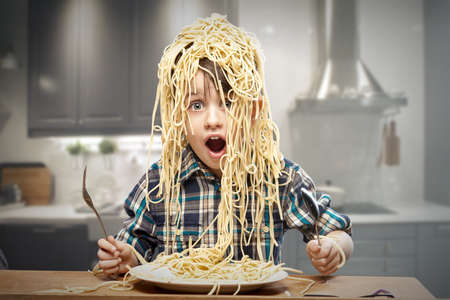 Foto de Surprised boy with pasta on the head - Imagen libre de derechos