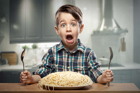 Photo pour Startled yound boy with noodles - image libre de droit