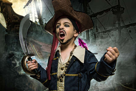 Foto de A angry young boy wearing a pirate costume. He stands on the background of the ship - Imagen libre de derechos