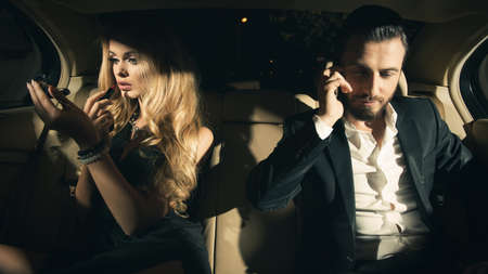 Photo pour couple in the car. Young woman applying lipstick and man using cell phone in car. - image libre de droit