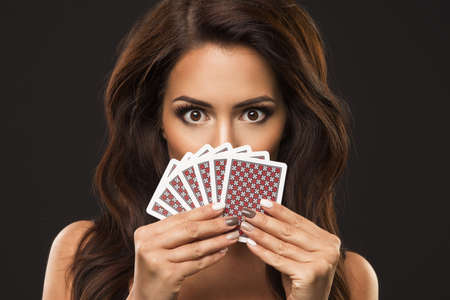 Foto de Beauty woman is hiding under playing cards, only eyes and poker face - Imagen libre de derechos