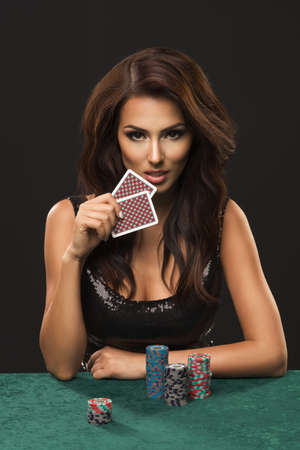 Foto de Sexy brunette woman with poker cards on black background - Imagen libre de derechos