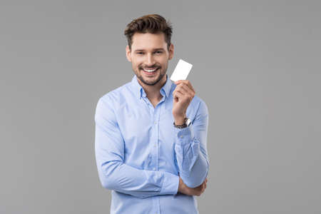 Photo pour Handsome man in blue shirt  with white card - image libre de droit