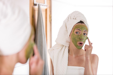 Photo pour The woman applies green organic face mask in the bathroom - image libre de droit