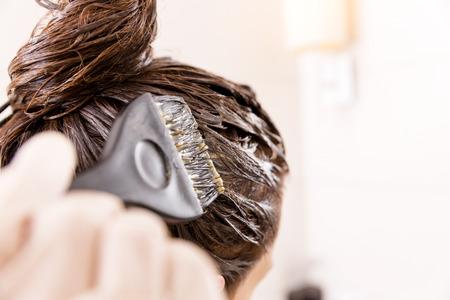 Foto de Woman with dying her hair in front of mirror in her own bathroom. - Imagen libre de derechos