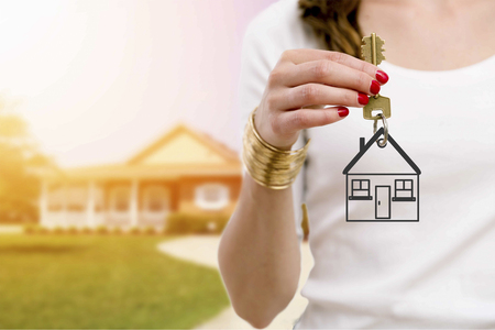 Foto de Real estate agent holding keys in front of a beautiful new home. - Imagen libre de derechos