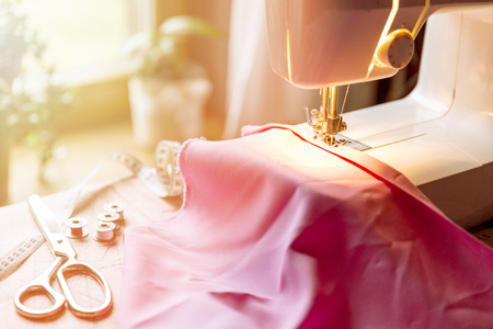 Photo for Tailoring Process - Women's hands behind her sewing machine - Royalty Free Image