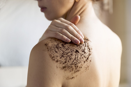 Photo pour Beauty, spa and healthy skin concept - woman cleans skin of the body with coffee scrub in bathroom. - image libre de droit
