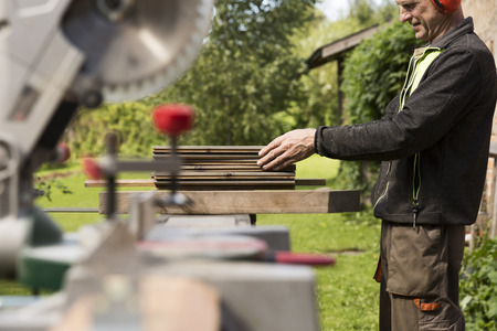 Photo for Senior men preparing wood materials with rotary saw - Royalty Free Image