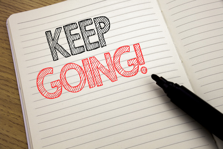Foto de Handwriting Announcement text showing Keep Going. Business concept for Go Moving Forward Letting written on notebook with space on book background with marker pen - Imagen libre de derechos