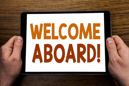 Photo for Hand writing text caption Welcome Aboard. Business concept for Greeting Join Member Written tablet laptop, wooden background with businessman hand, finger holding PC. - Royalty Free Image