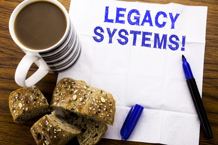 Foto de Handwritten text showing Legacy Systems. Business concept for Upgrade SOA Application written on tissue paper on wooden background with pen bread healthy coffee in the restaurant - Imagen libre de derechos