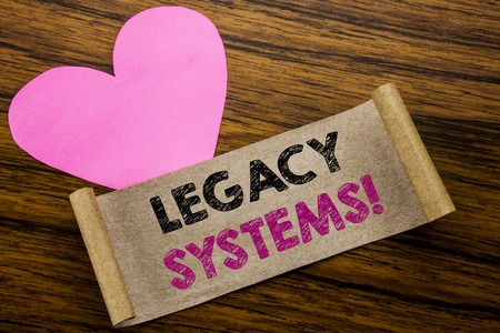Foto de Writing text showing Legacy Systems. Business concept for Upgrade SOA Application written on sticky note paper, wooden background. With pink heart meaning love adoration. - Imagen libre de derechos