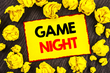 Foto de Handwriting Announcement text  Game Night. Conceptual photo Entertainment Fun Play Time Event For Gaming written Yellow Stikcy Note Folded Paper the wooden background - Imagen libre de derechos